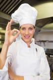 Uśmiechniętej kobiety kucbarski gestykuluje ok podpisuje wewnątrz kuchnię Fotografia Stock