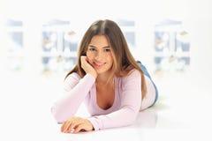 Uśmiechniętej młodej kobiety łgarski puszek na podłoga Obrazy Royalty Free