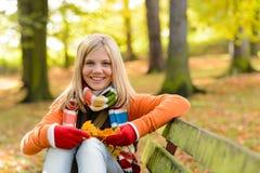 Uśmiechniętej nastolatek dziewczyny siedzącej jesieni parkowa ławka Obrazy Royalty Free