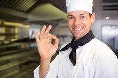 Uśmiechniętej samiec kucbarski gestykuluje ok podpisuje wewnątrz kuchnię Obrazy Stock