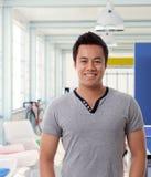 Uśmiechnięty azjatykci mężczyzna przy nowożytnym biurem Zdjęcie Royalty Free