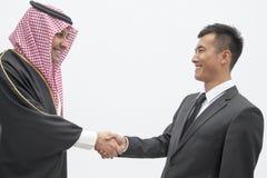 Uśmiechnięty biznesmen i młody człowiek w tradycyjnych Arabskich ubraniowych chwianie rękach, studio strzał Obrazy Stock