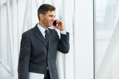 Uśmiechnięty biznesowy mężczyzna opowiada na telefonie komórkowym Fotografia Stock