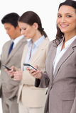 Uśmiechnięty bizneswoman z telefonem komórkowym obok kolegów Fotografia Stock