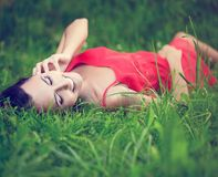 Uśmiechnięty brunetki dziewczyny lying on the beach w zielonej lato trawie Fotografia Stock