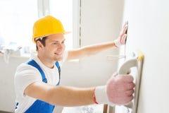 Uśmiechnięty budowniczy z śrutowania narzędziem indoors Obrazy Stock