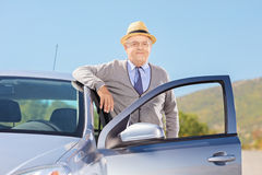 Uśmiechnięty dojrzały dżentelmen z kapeluszem pozuje obok jego samochodowego outside Obrazy Royalty Free