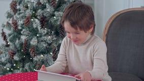 Uśmiechnięty dzieciak chłopiec obsiadanie na krześle i bawić się z pastylką podczas Bożenarodzeniowego czasu zbiory wideo