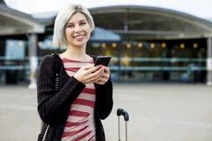 Uśmiechnięty Żeński podróżnik Używa Mądrze telefon Na zewnątrz dworca Obraz Stock