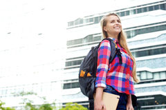 Uśmiechnięty żeńskiego ucznia chodzący outside z torbą i książką Obraz Royalty Free