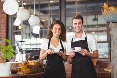 Uśmiechnięty kelner i kelnerka trzyma filiżankę kawy Fotografia Royalty Free
