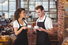 Uśmiechnięty kelner i kelnerka trzyma filiżankę kawy Zdjęcia Royalty Free