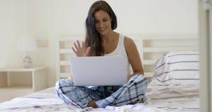 Uśmiechnięty kobiety falowanie w kierunku laptopu ekranu Obraz Royalty Free