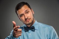 Uśmiechnięty mężczyzna gestykuluje z ręką, wskazuje palec przy kamerą Zdjęcia Stock