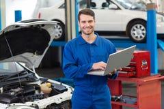 Uśmiechnięty mechanik używa jego laptop Zdjęcia Royalty Free