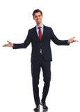 Uśmiechnięty młody biznesowy mężczyzna wita ciebie w kostiumu i krawacie Zdjęcia Stock
