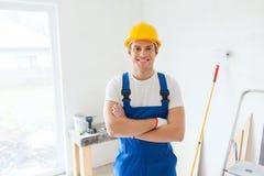Uśmiechnięty młody budowniczy w hardhat indoors Obraz Stock