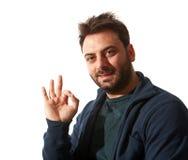 Uśmiechnięty młody człowiek gestykuluje ok szyldowego Fotografia Stock