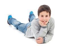 Uśmiechnięty preteen chłopiec lying on the beach na podłoga Fotografia Royalty Free