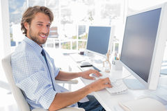 Uśmiechnięty projektant pracuje przy jego biurkiem Zdjęcia Royalty Free