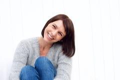 Uśmiechnięty w średnim wieku kobiety obsiadanie przeciw biel ścianie Obraz Royalty Free