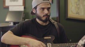 Umiejętność młody brodaty mężczyzna bawić się gitarę w barze Czas wolny przy piwnym pubem zbiory