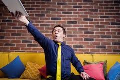 Umkippen betont, verärgerter Geschäftsmann, der seine digitale Tablette, U wirft lizenzfreie stockfotos