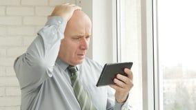 Umkippen-Geschäftsmann Use Electronic Tablet las das schlechte Nachrichten-on-line-Gestikulieren nervös stockfotos