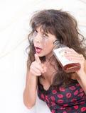 Umkippen getrunkene Frau mit Whisky-Flasche im Schlafzimmer Lizenzfreies Stockbild