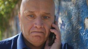 Umkippen-Mann, der die enttäuschte Unterhaltung mit Mobiltelefon auf der Straße schaut lizenzfreie stockfotos