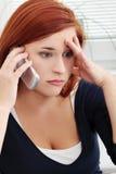 Umkippen und gesorgte junge Frau, die durch Telefon sprechen Stockbild