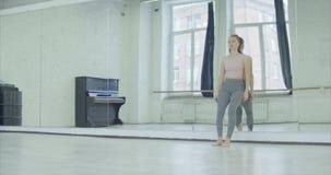 Umkippenfrau, die auf großem Spiegel im Tanzstudio sich lehnt stock video footage