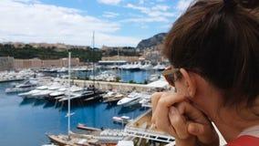 Umkippenfrau, die teure Yachten im Hafen, Reichtumsabstand, unerreichbarer Luxus betrachtet stock video footage