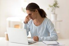 Umkippenfrauengefühl ermüdet nach Überstundencomputerarbeit stockfoto