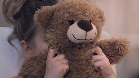 Umkippenmädchen, das hinter Teddybären sich versteckt und traurig Kamera, Annahmeprogramm betrachtet stock footage