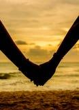 Umklammerte Hände auf dem Strand Lizenzfreie Stockbilder