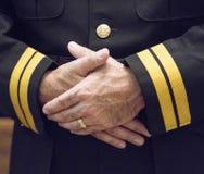 Umklammerte Hände in der Uniform Stockfoto