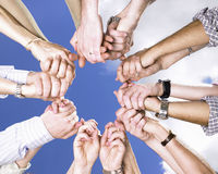 Umklammerte Hände in einem Kreis Stockbild