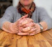 Umklammerte Hände einer älteren Dame, die an einem Tisch sitzt Stockbilder