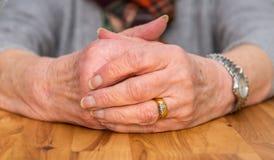 Umklammerte Hände eines weiblichen Pensionärs, der auf einer Tabelle stillsteht Lizenzfreie Stockfotos