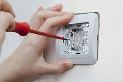 Ummauern Sie Montagehaushaltslichtschalter unter Verwendung des Schraubenziehers, elektrisch stockbild