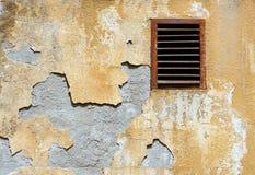 Ummauern Sie zerbröckelnden Gipsmantel und rostiges Belüftungsgitter Stockfotografie