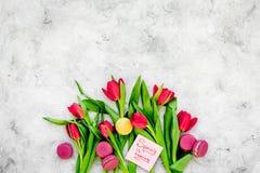 Umore della sorgente I tulipani vicino balzano è macarons venenti dell'iscrizione e dei dolci della mano sullo spazio grigio dell Fotografia Stock