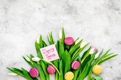 Umore della sorgente I tulipani vicino balzano è macarons venenti dell'iscrizione e dei dolci della mano sullo spazio grigio dell Immagini Stock Libere da Diritti