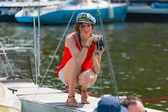 Umore di estate: una ragazza in blusa rossa che prende le immagini all'yacht club Immagine Stock