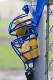 Umpire Mask. Umpire's mask hanging on backstop post, waiting for game to start royalty free stock photography