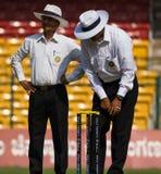 Umpires inspect. Cricket umpires Rajesh Deshpande and Vineet Kulkarni inspect the proceedings stock photography