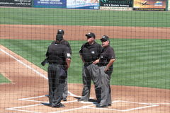 Umpires Meeting on the Other Side of the Backstop Royalty Free Stock Photos