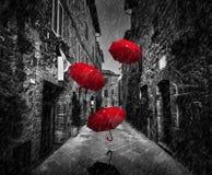 Umrbellas-Fliegen mit Wind und Regen auf dunkler Straße in einer alten italienischen Stadt in Toskana, Italien Stockbilder