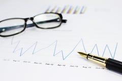 Umsatzdiagramme auf der Tabelle mit Feder Stockfotografie